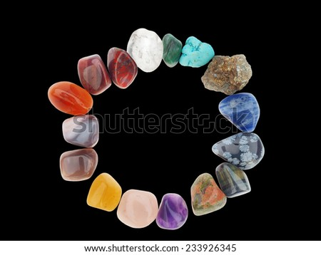 Color spectrum of semiprecious gemstones in circle frame, on black background  - stock photo