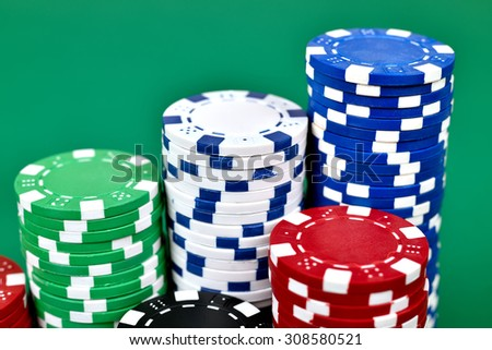 Color stacks of poker chips on green table