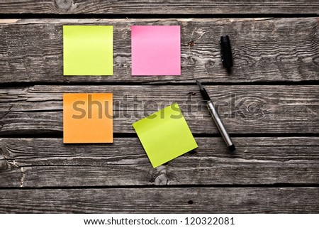 Color sticky note paper sheets fountain pen. Closeup on old wooden table. - stock photo