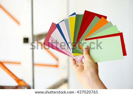 color swatches in a female hand over home background,renovation and decoration concept - stock photo
