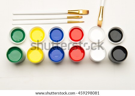 Color tempera water based paints with paintbrush on a white background - stock photo