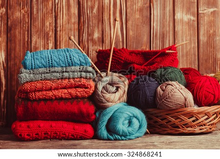 Color threads, knitting needles and clothes on the wooden table