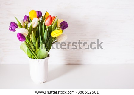 Color tulips in a white vase. Spring concept with copy space
