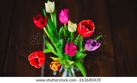 color tulips in vase on wooden table - stock photo