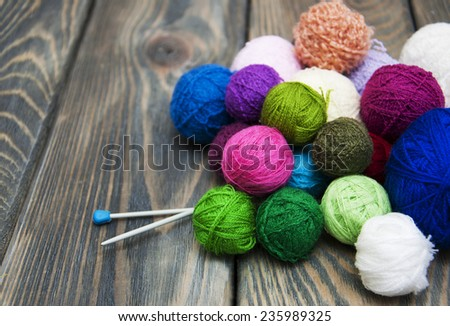 color woolen clews for knitting on a wooden background - stock photo