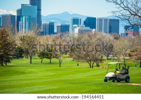 Colorado Golf Field with Denver Skyline and Golf Cart. - stock photo