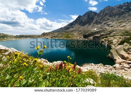 Colorado Rocky Mountain lake with waterfall and wildflowers blooming in the summer - stock photo