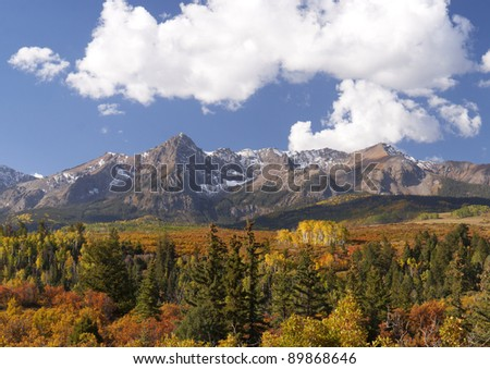 Colorado Rocky Mountains with brightly colored aspens and blue sky. - stock photo