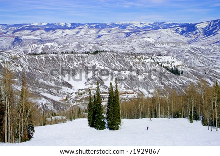 Colorado Ski Slope: The Rocky Mountains offer a panoramic view to skiers on a sunny day in Colorado. - stock photo
