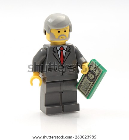 Colorado, USA - March 12, 2015: Studio shot of Lego businessman holding a money. Legos are a popular line of plastic construction toys manufactured by The Lego Group, a company based in Denmark. - stock photo