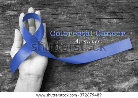 Colorectal/ Colon cancer awareness ribbon color splashed on human helping hand old aged background: Dark blue satin fabric symbolic concept raising campaign support people living w/ tumor illness - stock photo