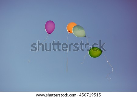 Colored balloons fly in the blue sky
