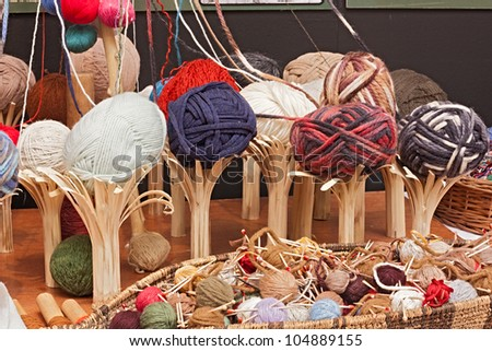 colored balls of wool on wooden rustic supports and in a basket with needles - a variety of yarns for knitting - stock photo