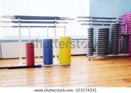 Colored barbel weights in gym - stock photo