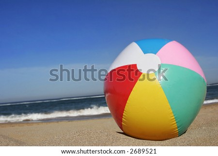 Colored beachball on golden sand beach with blue sky - stock photo