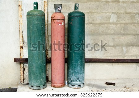 Colored big gaz bottles in the street, green, red - stock photo