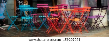 Colored bistro chairs in french market - stock photo