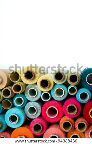 colored bobbins background. red, orange, blue and yellow colors. back ground divided in two parts. one part is white paper - stock photo