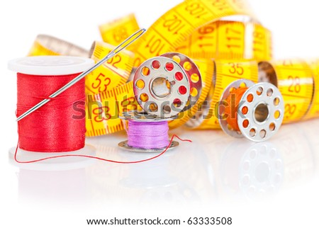 Colored bobbins for sewing and measuring tape over white background - stock photo