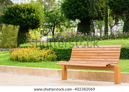 Colored brown bench with green park background