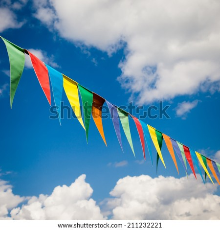 colored bunting triangular flags hanging on blue sky background - stock photo