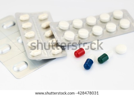 Colored capsules, pills medicines and blister photographed on a white background - stock photo