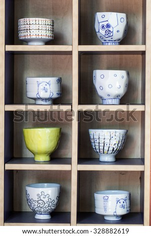 Colored ceramic cups on wooden showcase - stock photo
