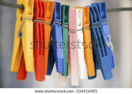colored clothe pins hanging on black rope on a blurred background , closeup capture