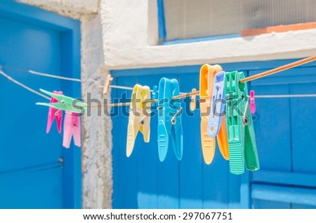 colored clothespins hanging on a rope on the background of the white house and the blue door - stock photo