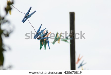 colored clothespins on rope, Colorful clothespin white blue sky, Colorful clothes pegs on a rope against blue sky with clouds - stock photo