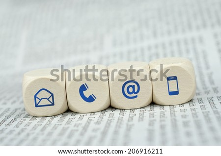 colored contact us cubes on newspaper - stock photo
