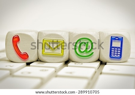 colored contact us symbols on cubes on a keyboard - stock photo