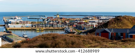colored Crab fisher hutches at harbor Island Helgoland, Germany, nordic style houses with boat and blue sky, panorama view from hill to north sea - stock photo