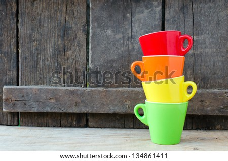 Colored cups on the wooden background.Selective focus - stock photo