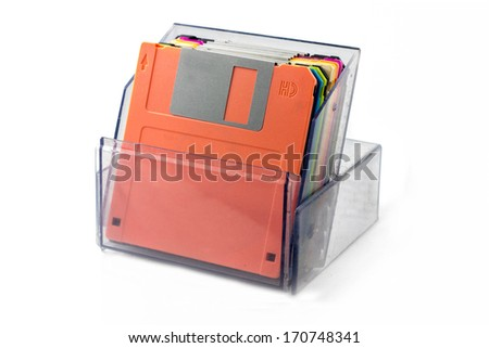 Colored diskettes in a transparent box isolated on white background. - stock photo