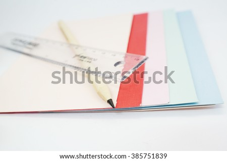 Colored drawing paper in a variety of colors in white isolated background with pencil and ruler - stock photo