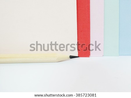 Colored drawing papers in a variety of colors in white isolated background with pencils - stock photo