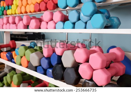 Colored dumbbells in a rack at the gym - stock photo
