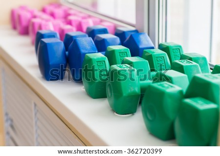 Colored dumbbells lying on a window at the gym. Dumbbells for fitness for women. - stock photo