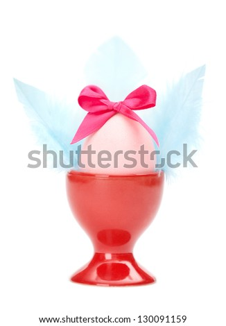 Colored easter egg with pink bow and blue wings in red egg cup, isolated on white. Traditional symbol of the feast - stock photo
