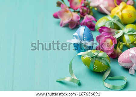 Colored Easter eggs and flowers on a turquoise table (horizontal shot) - stock photo