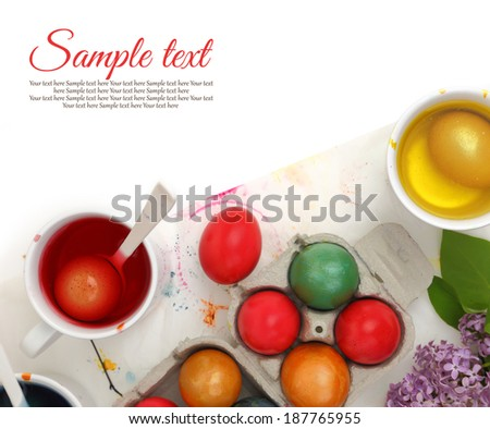 Colored Easter eggs and liquid color dyes on white background - stock photo