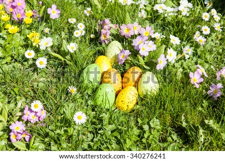 colored Easter eggs hidden in flowers and grass - stock photo