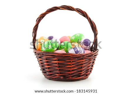 colored Easter eggs in a basket on a white background