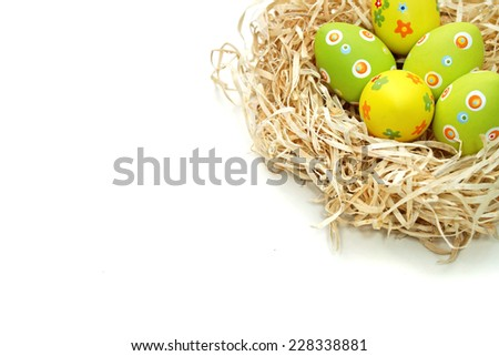 Colored Easter eggs into a nest from top corner on white background - stock photo
