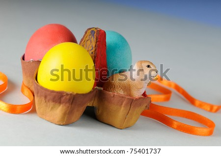 colored eggs and toy rabbit in easter egg stand - stock photo