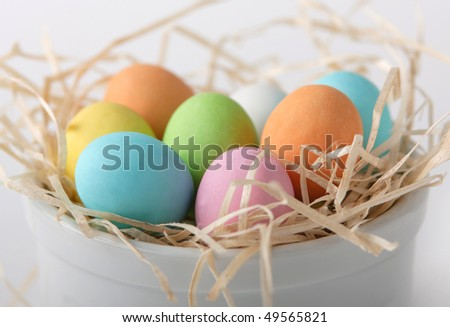 Colored eggs in a straw nest - stock photo