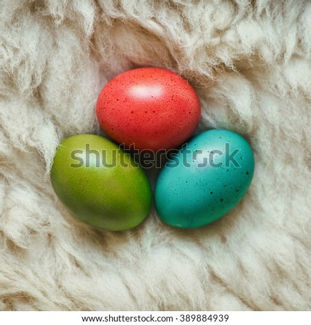 Colored eggs on natural fluffy sheep skin background. Easter postcard template. - stock photo