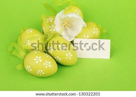 Colored eggs with decorative ornaments and beautiful tulips with card for your text on Easter - stock photo