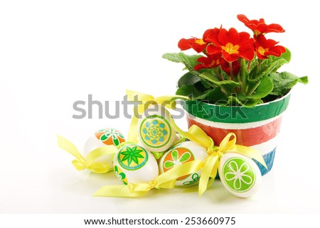 colored eggs with primrose flower in a pot on a white background - stock photo